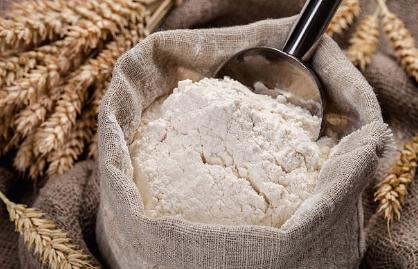 Image montrant de la farine blanche dans un sac en tissu, entouré de blé.